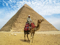 Camel Man in Front of Giza Pyramid. Cairo, Egypt - February 28th, 2008: Portrait of a camel man on his camel posing in front of the Pyramid of Khafre, the second Stock Photos