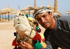 Camel owner portrait. Egyptian man and his camel on the beach of Sharm el Sheikh Stock Images