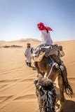 Camel ride. A girl riding a camel in Sahara desert near Merzouga, Morocco Royalty Free Stock Image