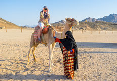 The camel ride. HURGHADA, EGYPT - OCTOBER 5, 2014: The tourist feels happy during the camel ride and the young girl-cameleer waves her hand to the friends, on royalty free stock photography