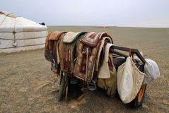 Camel saddles, Mongolia. A nomadic herder's camel saddles, propped on a trailer outside a ger in the Gobi Desert, Mongolia Royalty Free Stock Photo