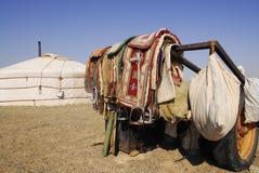 Camel saddles, Mongolia. A nomadic herder's camel saddles, propped on a trailer outside a ger in the Gobi Desert, Mongolia stock photography