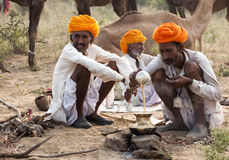 The camel traders of pushkar. Camel traders of Pushkar, Rajasthan, India wearing yellow turbans sitting on the fair ground and cooking Stock Photography