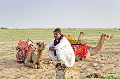 A Cameleer anxiously waits for tourists at Sam Desert, Jaisalmer, Rajasthan, India Stock Images