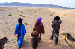 Cameleer. (camel driver) with camels in dunes of Marrakech Royalty Free Stock Photos
