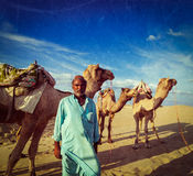 Cameleer (camel driver) with camels in dunes of Thar desert. Raj. Vintage retro hipster style travel image of Rajasthan travel background - Indian man cameleer ( Stock Photos