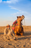 Cameleer sit beside camel Stock Photo
