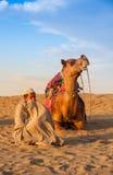 Cameleer zit naast kameel Stock Foto