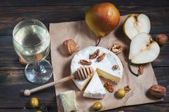 Camembert τυρί με τα ξύλα καρυδιάς, το μέλι και τα αχλάδια στον αγροτικό πίνακα Στοκ φωτογραφία με δικαίωμα ελεύθερης χρήσης