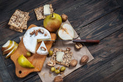 Camembert τυρί με τα ξύλα καρυδιάς, το μέλι και τα αχλάδια στον αγροτικό πίνακα Στοκ εικόνες με δικαίωμα ελεύθερης χρήσης