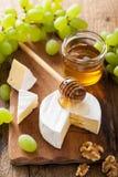 Camembert τυρί με τα σταφύλια, το μέλι και τα καρύδια στο ξύλινο backgroun Στοκ Φωτογραφία