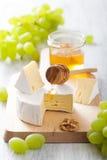 Camembert τυρί με τα σταφύλια, το μέλι και τα καρύδια στο ξύλινο backgroun Στοκ φωτογραφία με δικαίωμα ελεύθερης χρήσης
