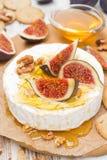 Camembert τυρί με το μέλι, τα σύκα και τα ξύλα καρυδιάς σε έναν ξύλινο πίνακα Στοκ εικόνα με δικαίωμα ελεύθερης χρήσης