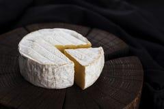 Camembert τυρί στο μαύρο ξύλινο υπόβαθρο, με το διάστημα αντιγράφων πεδίο βάθους ρηχό στοκ φωτογραφίες