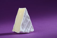 Camembert. Cheese on purple background. Copy space Stock Image