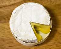 Camembert. A rich, soft, creamy french cheese with a whitish rind on a wooden surface royalty free stock images