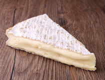 Camembert. Slice of camembert on wooden background Royalty Free Stock Photos