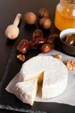 Camembert avec du miel, des dates et des écrous sur le fond foncé Image libre de droits