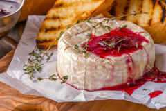 Camembert with berry jam, toast and thyme. Royalty Free Stock Photos