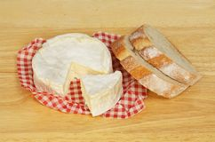 Camembert and bread. Camembert cheese and bread on a wooden chopping board royalty free stock photography