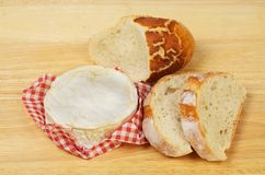 Camembert and bread. Camembert cheese and crusty bread on a wooden chopping board royalty free stock photo