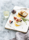 Camembert or brie cheese with fresh figs, honeycomb and glass of white wine on serving board over grunge rustic grey Stock Photos