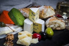 Mix cheese on dark background on wood board with grapes, honey, nuts, tomatoes and basil. Top view stock image