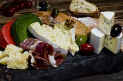 Mix cheese and meat on dark background on wood board with grapes, honey, nuts, tomatoes and basil. Top view. stock photo