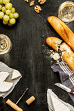Camembert cheese, baguettes and wine on black Royalty Free Stock Photo