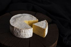Camembert cheese on black wooden background, with copy space. Shallow depth of field Stock Photography