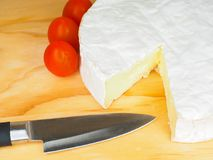 Camembert cheese on board. Wheel of Camembert cheese on wooden cutting board with whole cherry tomatoes and knife Stock Photo