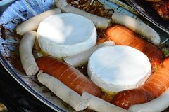 Camembert cheese, bratwurst and sausages prepared on alluminium plate for barbecue, grilled chicken breast in background Royalty Free Stock Photos