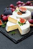 Camembert cheese and cut a slice on stone serving board Royalty Free Stock Photo