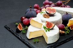 Camembert cheese and cut a slice on stone serving board Stock Photography