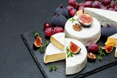 Camembert cheese and cut a slice on stone serving board Stock Image