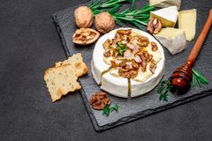 Camembert cheese and walnuts on stone serving board stock photo