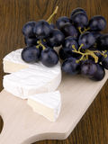 Camembert cheese with dark grapes Royalty Free Stock Photo