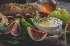 Camembert cheese, figs,prosciutto ,honey on dark serving board close up Royalty Free Stock Photography