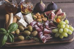 Camembert cheese, figs,prosciutto ,honey,olives, grapes and homemade bread, on dark serving board over rustic wooden background Royalty Free Stock Photography
