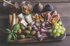 Camembert cheese, figs,prosciutto ,honey,olives, grapes and homemade bread, on dark serving board over rustic wooden background Stock Photos