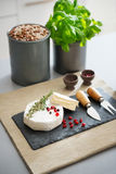 Camembert cheese with fresh herbs, pomegranate, and peppercorns Stock Photos