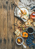 Camembert cheese, fruits, bread, honey, jam and wine, copy space Stock Images