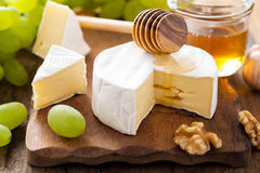Camembert cheese with grapes, honey and nuts on wooden backgroun Royalty Free Stock Images