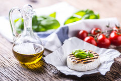 Camembert cheese. Grilled camembert cheese with olive oil and basil leaves Royalty Free Stock Images