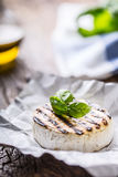 Camembert cheese. Grilled camembert cheese with olive oil and basil leaves Stock Image