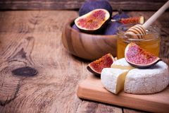 Camembert cheese with honey and figs on a wooden board. Royalty Free Stock Photo