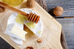 Camembert cheese with honey on a wooden board Royalty Free Stock Images