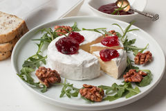 Camembert. Cheese on the plate with fruits and nuts royalty free stock photos
