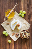 Camembert cheese with walnuts, honey and grapes Stock Photo