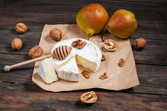 Camembert cheese with walnuts, honey and pears on rustic table Royalty Free Stock Photography